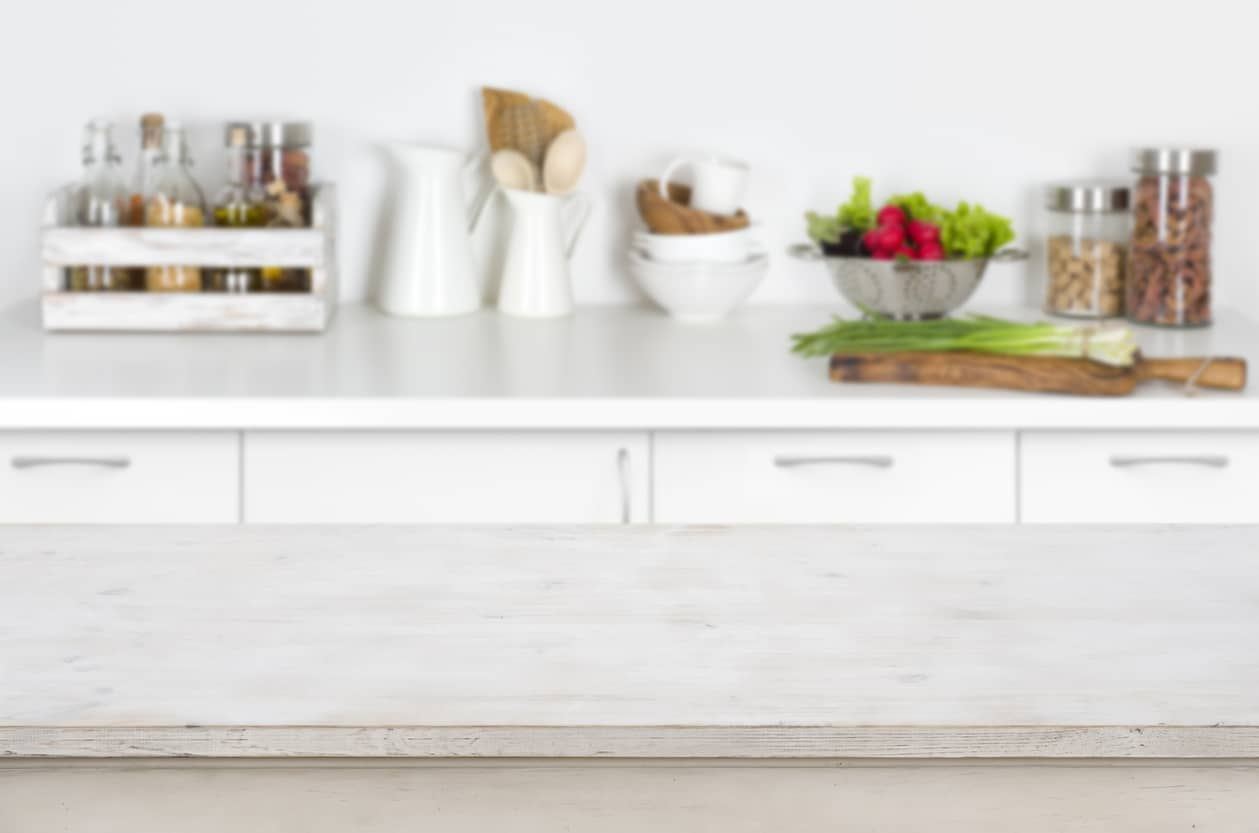 Wooden-table-on-blurred-kitchen-interior-background-with-fresh-vegetables-647234646_1261x835